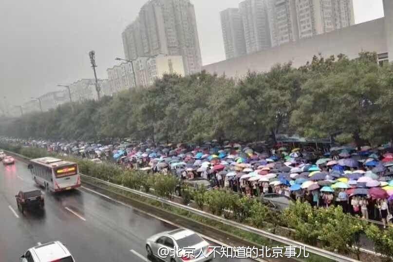 雨天早高峰的北京地铁1号线地铁站外的雨伞